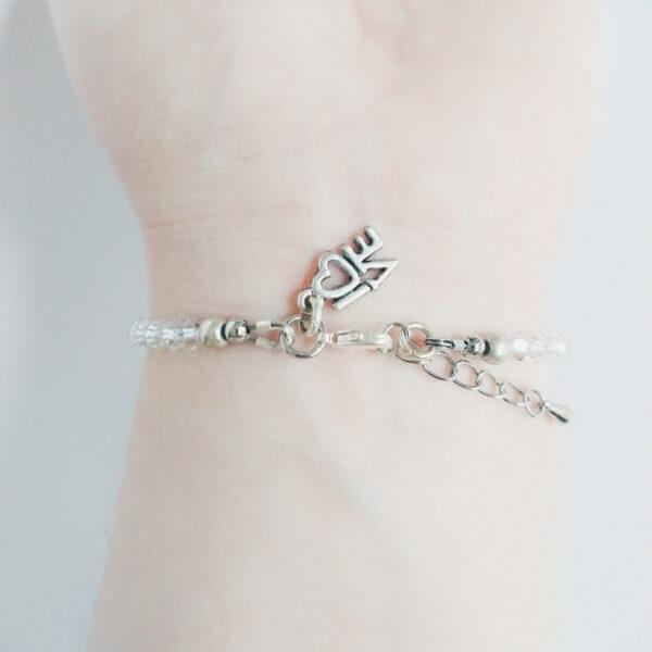 """Een armband met kleine 4 mm ronde kraaltjes in crystal moonlight (doorzichtig met een sprankel). Met een metalen bedeltje in de vorm van het woord """"Love"""". De onderkant van de armband wordt getoond om de pols van een blanke vrouw."""