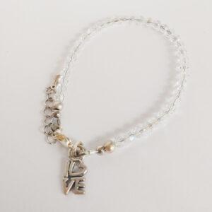 """Een armband met kleine 4 mm ronde kraaltjes in crystal moonlight (doorzichtig met een sprankel). Met een metalen bedeltje in de vorm van het woord """"Love"""".."""