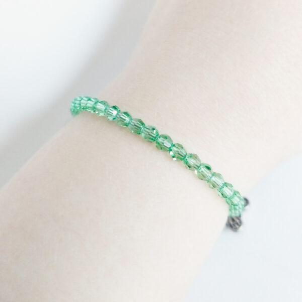 Een armband met kleine 4 mm ronde kraaltjes in peridot (een licht groene kleur). De armband wordt getoond om de pols van een blanke vrouw.
