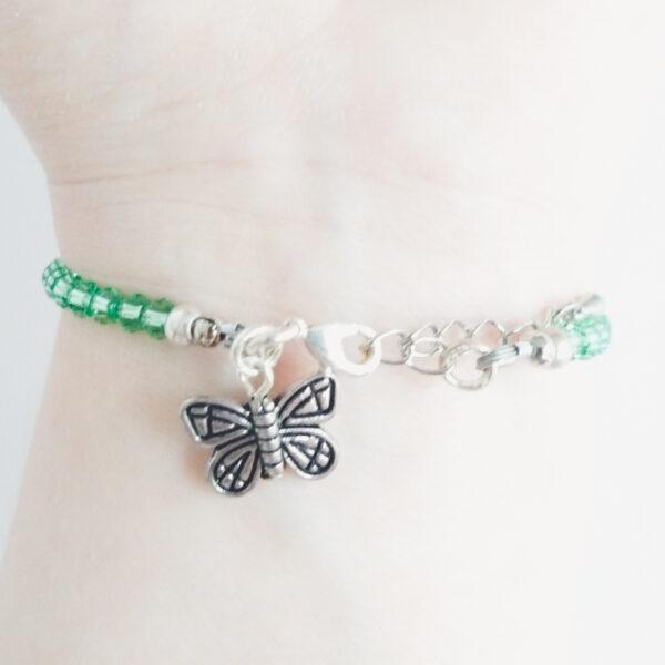 Een armband met kleine 4 mm ronde kraaltjes in peridot (een licht groene kleur). Met een metalen bedeltje in de vorm van een vlinder. De onderkant van de armband wordt getoond om de pols van een blanke vrouw.