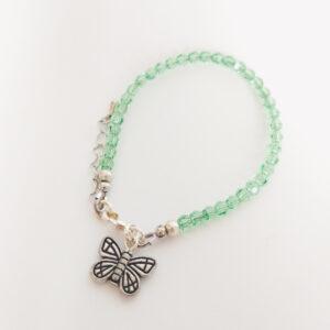 Een armband met kleine 4 mm ronde kraaltjes in peridot (een licht groene kleur). Met een metalen bedeltje in de vorm van een vogel.