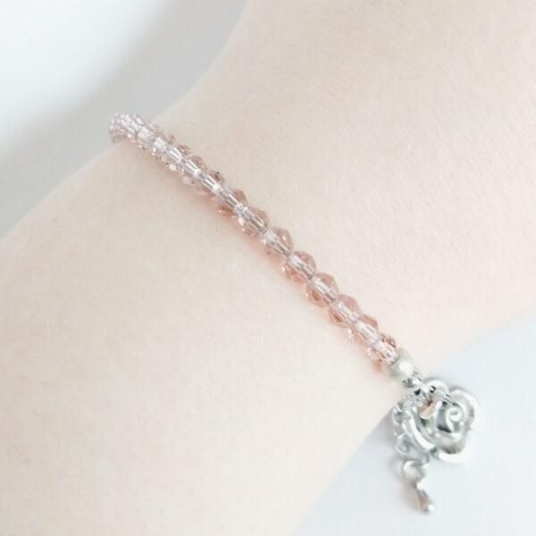Armband swarovski round antique pink. Een armband met kleine 4 mm ronde kraaltjes in antique pink (een oud roze kleur). De armband wordt getoond om de pols van een blanke vrouw.