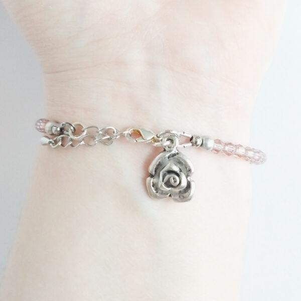 Een armband met kleine 4 mm ronde kraaltjes in antique pink (een oud roze kleur). Met een metalen bedeltje in de vorm van een roos. De onderkant van de armband wordt getoond om de pols van een blanke vrouw.
