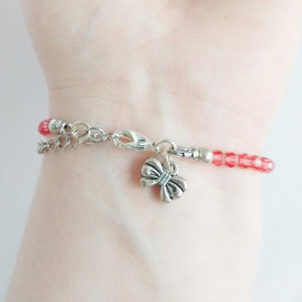 Een armband met kleine 4 mm ronde kraaltjes in padparadscha (een oranje-roze kleur). Met een metalen bedeltje in de vorm van een strikje. De onderkant van de armband wordt getoond om de pols van een blanke vrouw.