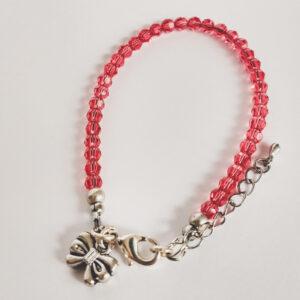 Een armband met kleine 4 mm ronde kraaltjes in padparadscha (een oranje-roze kleur). Met een metalen bedeltje in de vorm van een strikje.