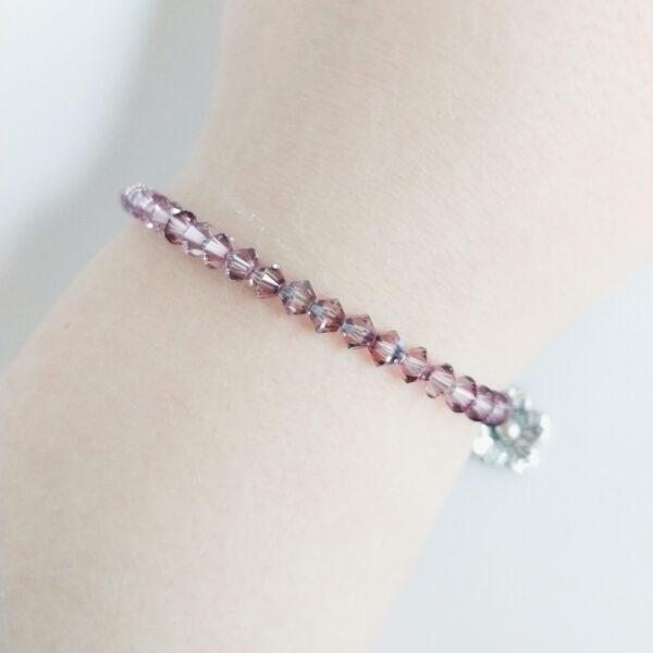Armband swarovski xilion oud roze. Een armband met kleine 4 mm hoekige kraaltjes in antique pink (een oud roze kleur). De armband wordt getoond om de pols van een blanke vrouw.