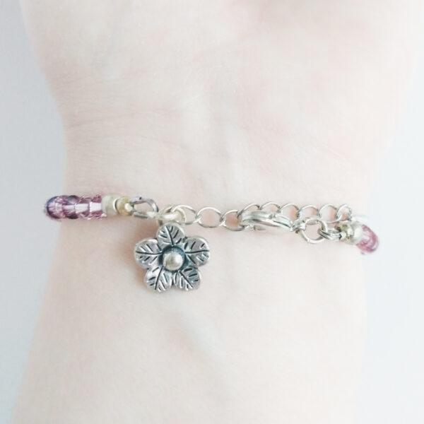 Armband swarovski xilion oud roze. Een armband met kleine 4 mm hoekige kraaltjes in antique pink (een oud roze kleur). Met een metalen bedeltje in de vorm van een bloem. De onderkant van de armband wordt getoond om de pols van een blanke vrouw.