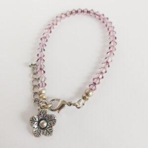 Armband swarovski xilion oud roze. Een armband met kleine 4 mm hoekige kraaltjes in antique pink (een oud roze kleur). Met een metalen bedeltje in de vorm van een bloem.