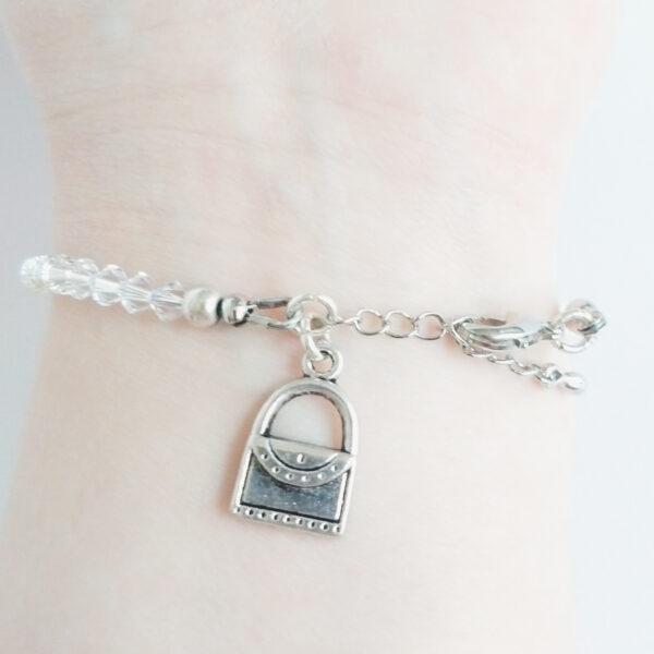Armband swarovski xilion kristal. Een armband met kleine 4 mm hoekige kraaltjes in crystal moonlight (een kristal kleur). Met een metalen bedeltje in de vorm van een handtasje. De onderkant van de armband wordt getoond om de pols van een blanke vrouw.
