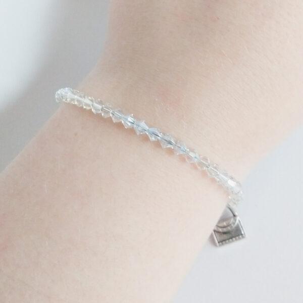 Armband swarovski xilion kristal. Een armband met kleine 4 mm hoekige kraaltjes in crystal moonlight (een kristal kleur). De armband wordt getoond om de pols van een blanke vrouw.