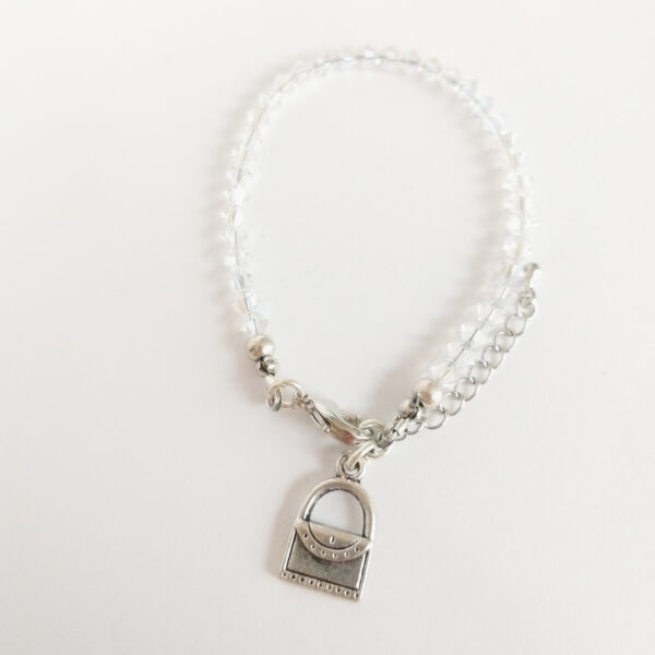 Armband swarovski xilion kristal. Een armband met kleine 4 mm hoekige kraaltjes in crystal moonlight (een kristal kleur). Met een metalen bedeltje in de vorm van een handtasje.