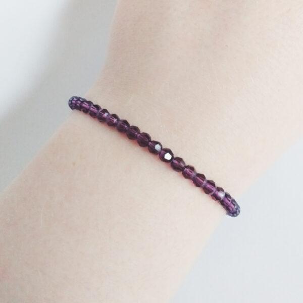 Armband swarovski round amethyst. Een armband met kleine 4 mm ronde kraaltjes in amethyst (een donker paarse kleur). De armband wordt getoond om de pols van een blanke vrouw.