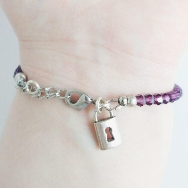 Een armband met kleine 4 mm ronde kraaltjes in amethyst (donker paarse kleur). Met een metalen bedeltje in de vorm van een slotje. De onderkant van de armband wordt getoond om de pols van een blanke vrouw.