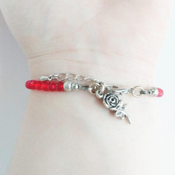 Een armband met kleine 4 mm ronde kraaltjes in siam (rode kleur). Met een metalen bedeltje in de vorm van een roos. De onderkant van de armband wordt getoond om de pols van een blanke vrouw.