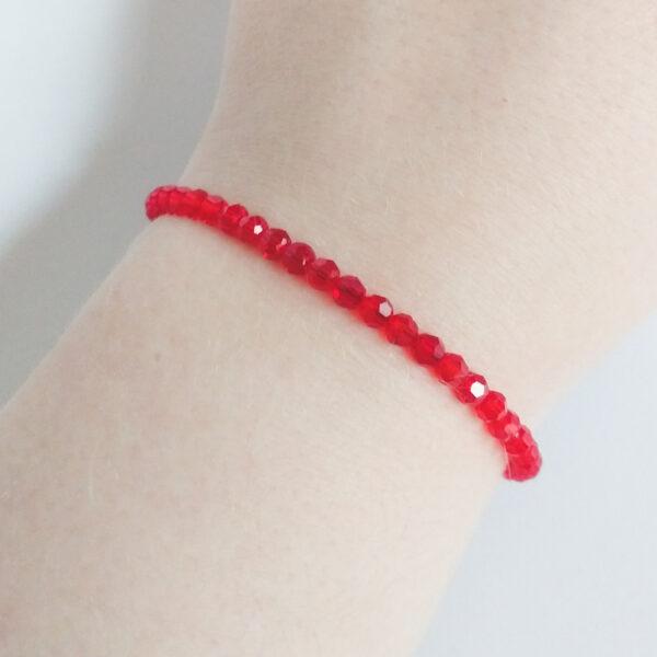Een armband met kleine 4 mm ronde kraaltjes in siam (een rode kleur). De armband wordt getoond om de pols van een blanke vrouw.
