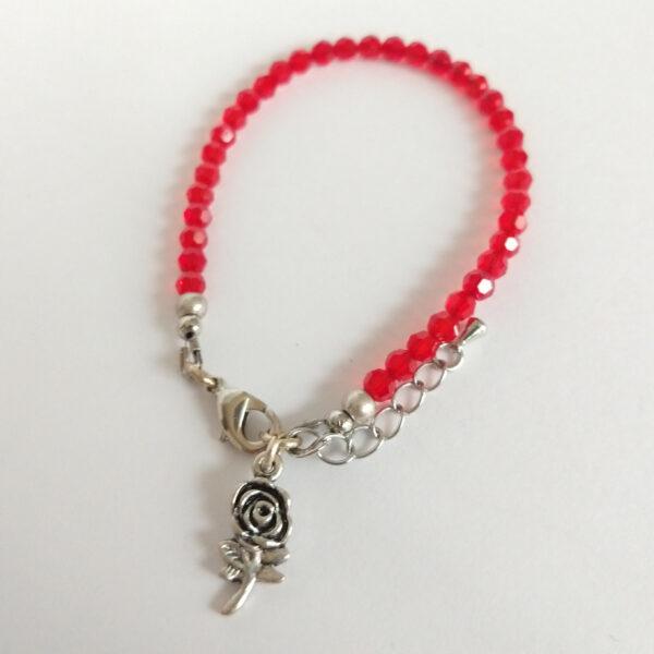 Een armband met kleine 4 mm ronde kraaltjes in siam (een rode kleur). Met een metalen bedeltje in de vorm van een roos.