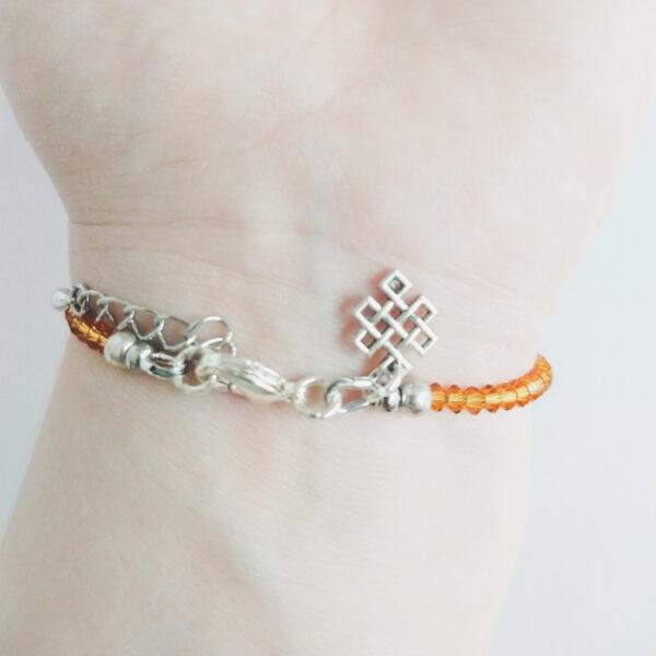 Armband swarovski xilion bruin oranje. Een armband met kleine 3 mm hoekige kraaltjes in topaz (een bruin oranje kleur). Met een metalen bedeltje in de vorm van een oneindige knoop. De onderkant van de armband wordt getoond om de pols van een blanke vrouw.