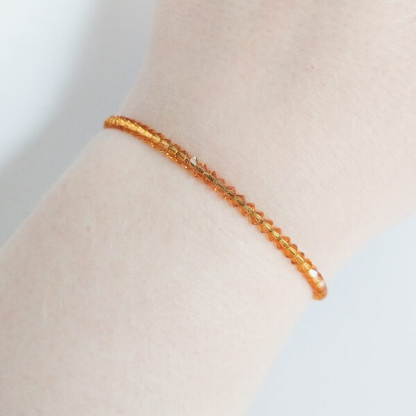 Armband swarovski xilion bruin oranje. Een armband met kleine 3 mm hoekige kraaltjes in topaz (een bruine oranje kleur). De armband wordt getoond om de pols van een blanke vrouw.