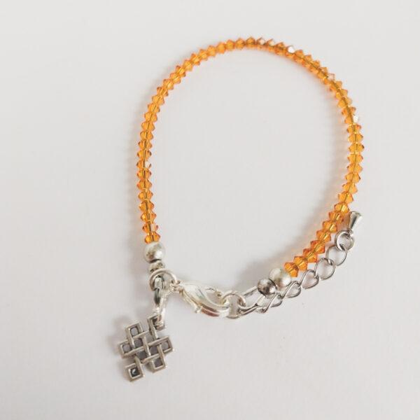 Armband swarovski xilion bruin oranje. Een armband met kleine 3 mm hoekige kraaltjes in topaz (een bruin oranje kleur). Met een metalen bedeltje in de vorm van een oneindige knoop.