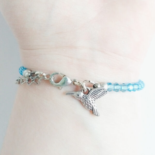 Een armband met kleine 4 mm ronde kraaltjes in aquamarine (een licht blauwe kleur). Met een metalen bedeltje in de vorm van een vogel. De onderkant van de armband wordt getoond om de pols van een blanke vrouw.