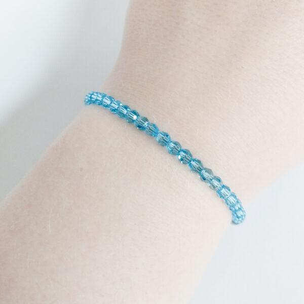 Een armband met kleine 4 mm ronde kraaltjes in aquamarine (een licht blauwe kleur). De armband wordt getoond om de pols van een blanke vrouw.
