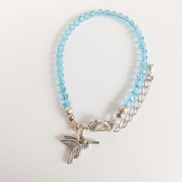 Een armband met kleine 4 mm ronde kraaltjes in aquamarine (een licht blauwe kleur). Met een metalen bedeltje in de vorm van een vogel.