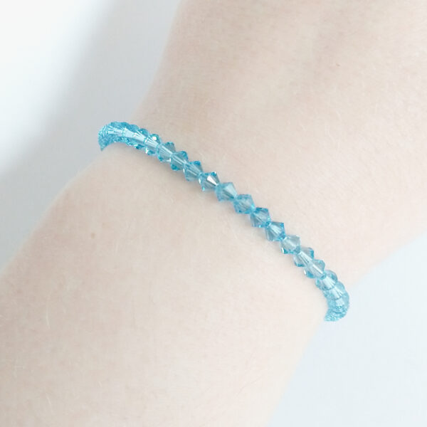 Armband swarovski xilion licht blauw. Een armband met kleine 4 mm hoekige kraaltjes in aquamarine (een licht blauw kleur). De armband wordt getoond om de pols van een blanke vrouw.