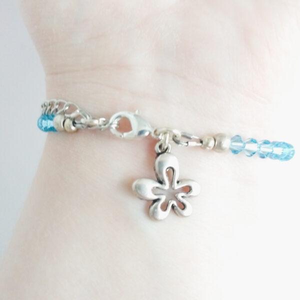 Armband swarovski xilion licht blauw. Een armband met kleine 4 mm hoekige kraaltjes in aquamarine (een licht blauwe kleur). Met een metalen bedeltje in de vorm van een bloem. De onderkant van de armband wordt getoond om de pols van een blanke vrouw.