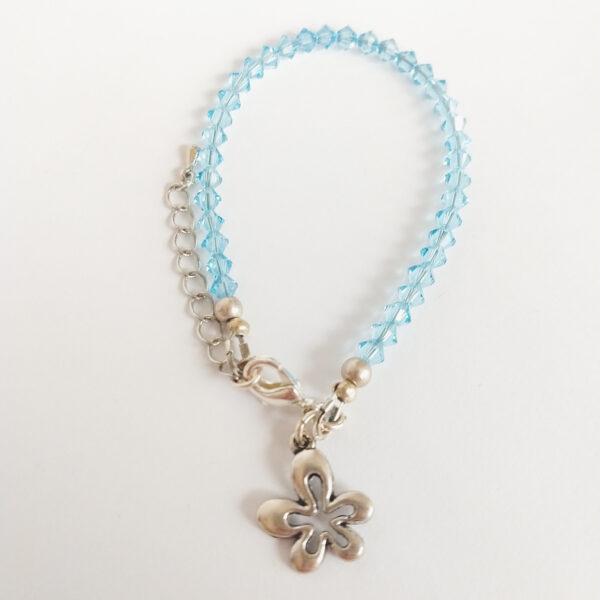 Armband swarovski xilion licht blauw. Een armband met kleine 4 mm hoekige kraaltjes in aquamarine (een licht blauw kleur). Met een metalen bedeltje in de vorm van een bloem.