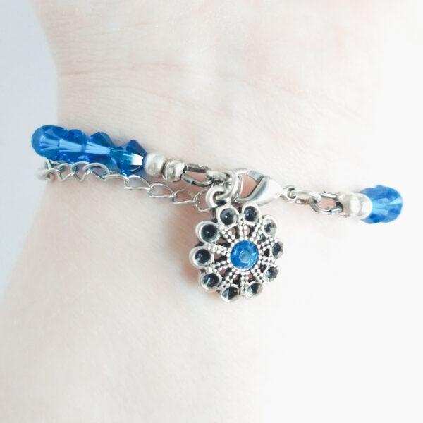 Armband swarovski xilion 6 mm blauw. Een armband met 6 mm hoekige kraaltjes in capri blue (een blauw kleur). Met een metalen bedeltje in de vorm van een bloem met een klein blauw steentje. De onderkant van de armband wordt getoond om de pols van een blanke vrouw.