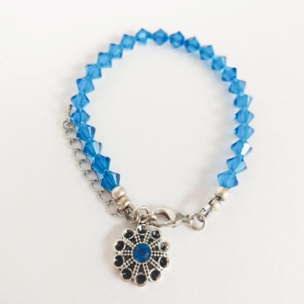 Armband swarovski xilion 6 mm blauw. Een armband met 6 mm hoekige kraaltjes in capri blue (een blauwe kleur). Met een metalen bedeltje in de vorm van een bloem met een blauw steentje.