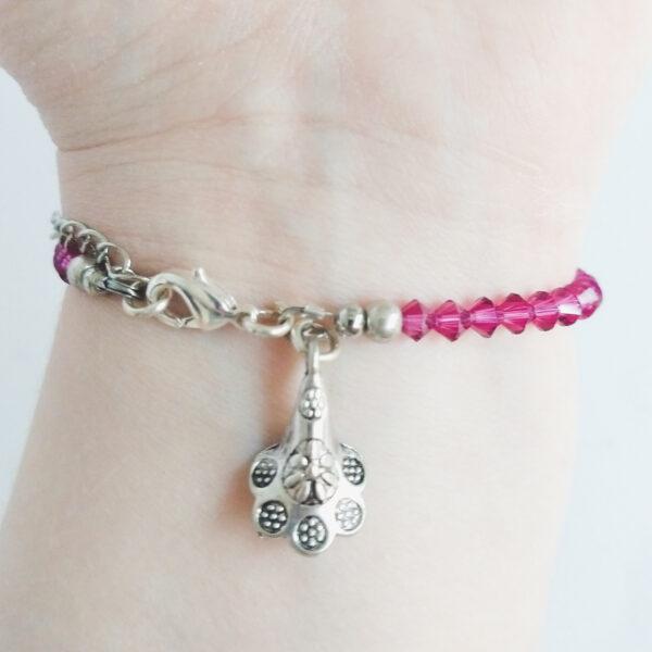 Armband swarovski xilion donker roze. Een armband met kleine 4 mm hoekige kraaltjes in fuchsia (een donker roze kleur). Met een metalen bedeltje in de vorm van een bloem. De onderkant van de armband wordt getoond om de pols van een blanke vrouw.