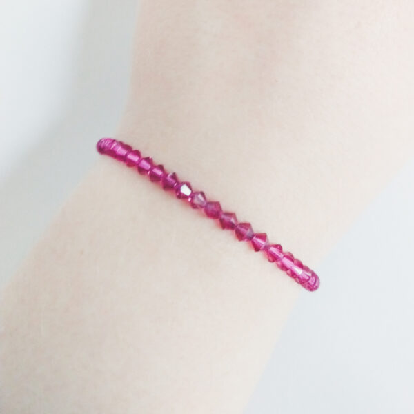 Armband swarovski xilion donker roze. Een armband met kleine 4 mm hoekige kraaltjes in fuchsia (een donker roze kleur). De armband wordt getoond om de pols van een blanke vrouw.