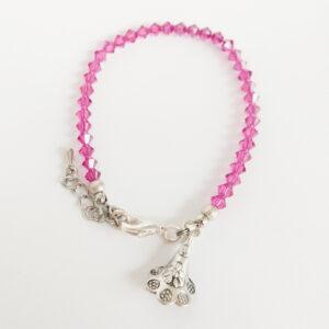 Armband swarovski xilion donker roze. Een armband met kleine 4 mm hoekige kraaltjes in fuchsia (een donker roze kleur). Met een metalen bedeltje in de vorm van een bloem.