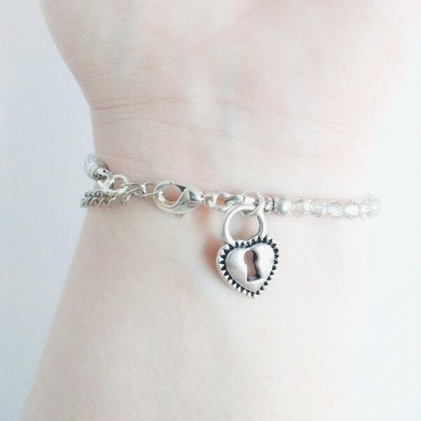Een armband met kleine 4 mm ronde kraaltjes in crystal silver shade (doorzichtig met een grijzige kleur). Met een metalen bedeltje in de vorm van een hartvormig slotje. De onderkant van de armband wordt getoond om de pols van een blanke vrouw.