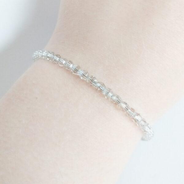 Armband swarovski round crystal silver shade. Een armband met kleine 4 mm ronde kraaltjes in crystal silver shade (doorzichtig met een grijzige kleur). De armband wordt getoond om de pols van een blanke vrouw.