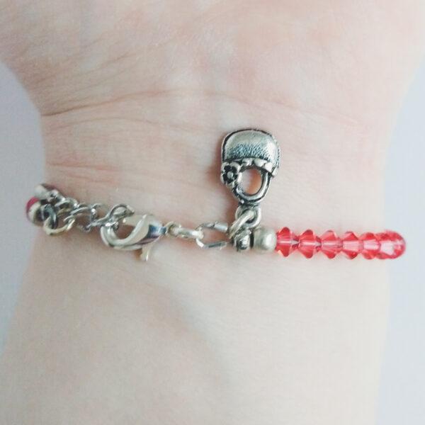 Armband swarovski xilion oranje roze. Een armband met kleine 4 mm hoekige kraaltjes in padparadscha (een oranje roze kleur). Met een metalen bedeltje in de vorm van een mandje. De onderkant van de armband wordt getoond om de pols van een blanke vrouw.