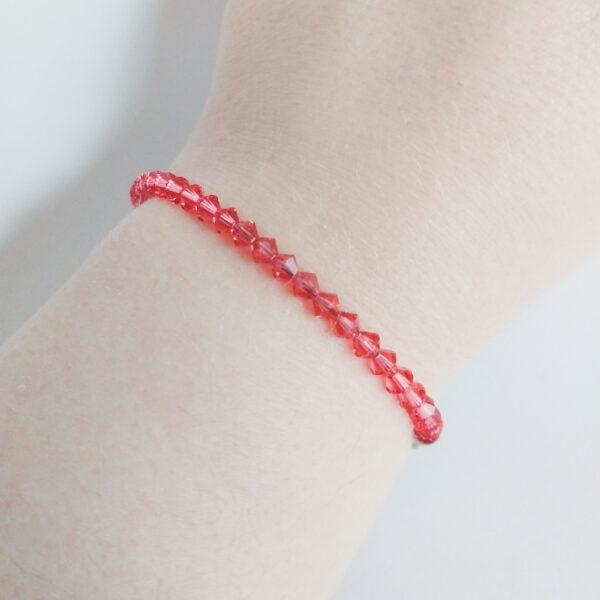Armband swarovski xilion oranje roze. Een armband met kleine 4 mm hoekige kraaltjes in padparadscha (een oranje roze kleur). De armband wordt getoond om de pols van een blanke vrouw.