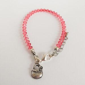 Armband swarovski xilion oranje roze. Een armband met kleine 4 mm hoekige kraaltjes in padparadscha (een oranje roze kleur). Met een metalen bedeltje in de vorm van een mandje.