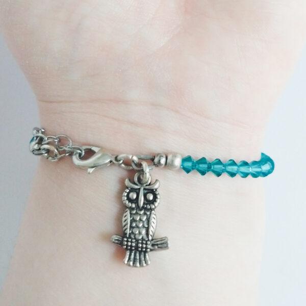 Een armband met kleine 4 mm ronde kraaltjes in blue zirkon (een blauw groene kleur). Met een metalen bedeltje in de vorm van een uiltje. De onderkant van de armband wordt getoond om de pols van een blanke vrouw.