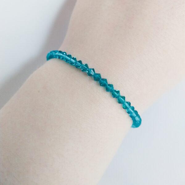 Armband swarovski xilion blauw groen. Een armband met kleine 4 mm hoekige kraaltjes in indicolite (een blauw groene kleur). De armband wordt getoond om de pols van een blanke vrouw.