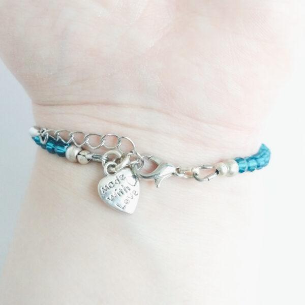 """Een armband met kleine 4 mm ronde kraaltjes in indicolite (een blauw groene kleur). Met een metalen bedeltje in de vorm van een hartje met de tekst """"Made with love"""" erop. De onderkant van de armband wordt getoond om de pols van een blanke vrouw."""