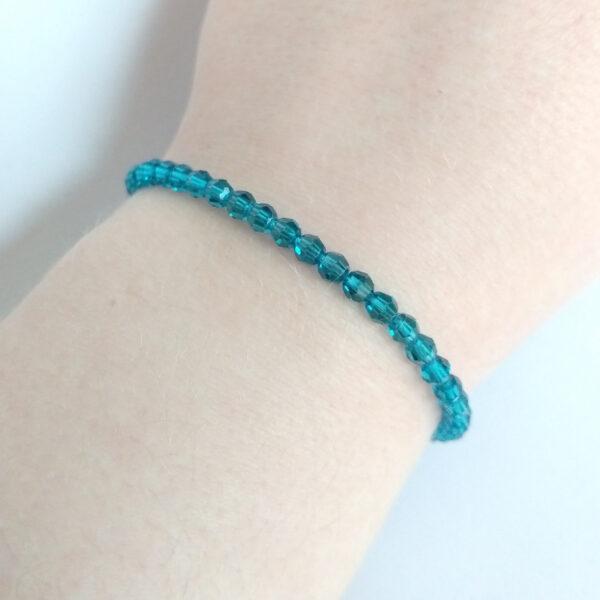 Een armband met kleine 4 mm ronde kraaltjes in indicolite (een blauw groene kleur). De armband wordt getoond om de pols van een blanke vrouw.