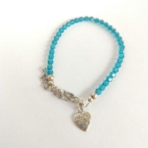 """Een armband met kleine 4 mm ronde kraaltjes in indicolite (een blauw groene kleur). Met een metalen bedeltje in de vorm van een hartje met de tekst """"Made with love"""" erop."""