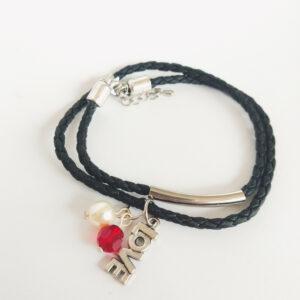 """Armband leer swarovski kraal rood en parel wit. Armbandje van gevlochten zwart leer met een 8 mm ronde (round) swarovski kraal in de kleur siam (rood) en een 8 mm parel in de kleur white (wit). Er hangt een leuk bedeltje aan van het woord """"Love"""" en op het leer zit een metalen buisje."""