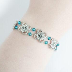 Armband bloemen swarovski blauw groen. Armband met metalen bloemen met er tussen kleine swarovski kraaltjes in de kleur indicolite (blauw groen). Er zit een metalen kraal bij het slotje. De armband is te zien om de pols van een blanke vrouw.
