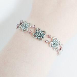Armband bloemen swarovski paars. Armband met metalen bloemen met er tussen kleine swarovski kraaltjes in de kleur antique pink (paars). Er zit een metalen kraal bij het slotje.De armband wordt getoond om de pols van een blanke vrouw.