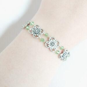 Armband bloemen swarovski licht groen. Armband met metalen bloemen met er tussen kleine swarovski kraaltjes in de kleur peridot (licht groen). Er zit een metalen kraal bij het slotje.De armband wordt getoond om de pols van een blanke vrouw.