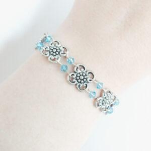 Armband bloemen swarovski licht blauw. Armband met metalen bloemen met er tussen kleine swarovski kraaltjes in de kleur aquamarine (licht blauw). Er zit een metalen kraal bij het slotje.De armband wordt getoond om de pols van een blanke vrouw.