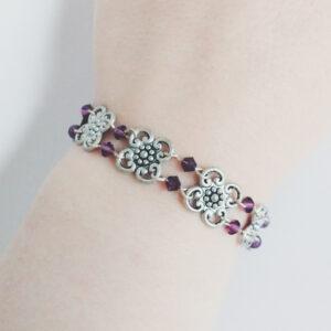 Armband bloemen swarovski donker paars. Armband met metalen bloemen met er tussen kleine swarovski kraaltjes in de kleur amethyst (donker paars). Er zit een metalen kraal bij het slotje.De armband wordt getoond om de pols van een blanke vrouw.
